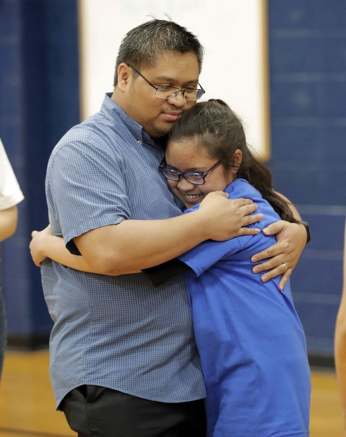 Marsha Tagala, 11, gets a hug from her father, Marc, after she learned she won the 2019 Illinois Google Doodle competition. The surprise announcement was made Thursday during a student assembly at West Oak Middle School in Mundelein.