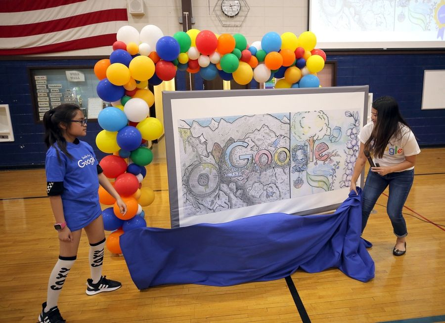 11-year-old Marsha Tagala, left, unveils her Google Doodle entry with Jackie Lau of Google on Thursday during a student assembly at West Oak Middle School in Mundelein.