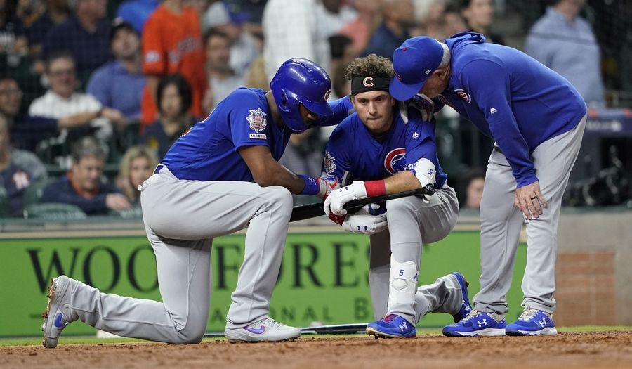 Chicago Cubs' Albert Almora Jr., center, takes a knee as Jason Heyward, left, and manager Joe Maddon talk to him after hitting a foul ball that hit a little girl in the stands off left field Wednesday in Houston.