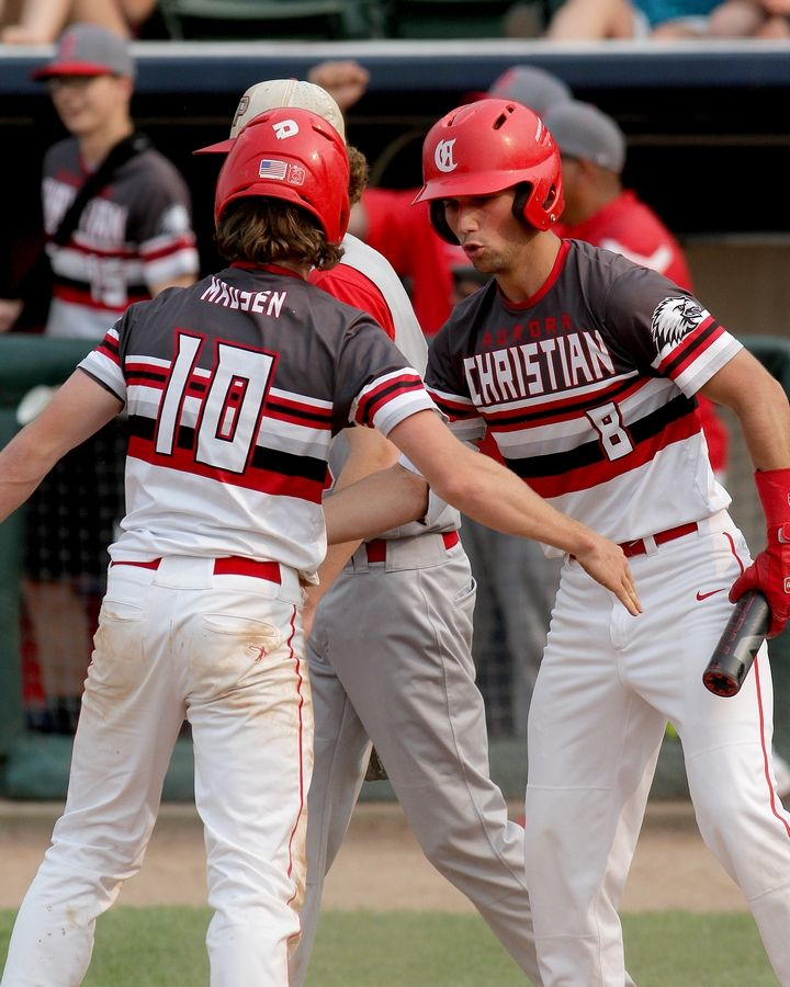 Aurora Christian's Sam Tickel congratulates teammate Trey Madsen after scoring a run in their Class 2A state semifinal baseball game against Pleasant Plains. The Eagles advance to Saturday's IHSA third place contest after falling to the Cardinals, 6-3.