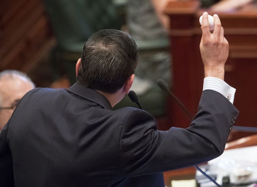 "Illinois state Rep. Anthony DeLuca, D-Chicago Heights, holds up an egg before cracking it into a pan to reference the ""This is your brain on drugs,"" campaign during debate on a bill to legalize recreational marijuana use in the Illinois House chambers Friday, May 31, 2019. DeLuca voted against the bill that passed the House 66-47. (Ted Schurter/The State Journal-Register via AP)"