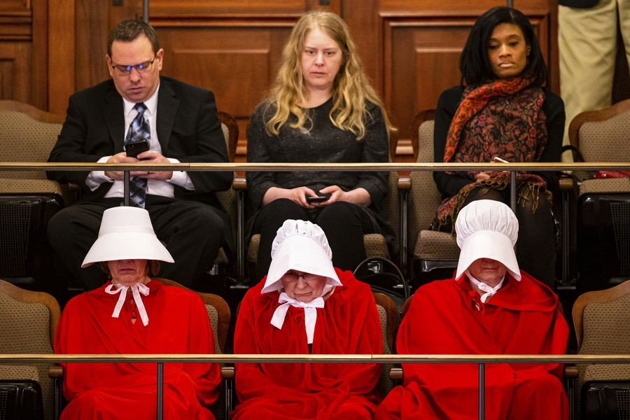 "People dressed as characters from ""The Handmaid's Tale"" sit in the president's gallery of the Senate showing their support of the Reproductive Health Act on the last scheduled day of the spring session at the State Capitol, Friday, May 31, 2019, in Springfield, Ill. (Justin Fowler/The State Journal-Register via AP)"