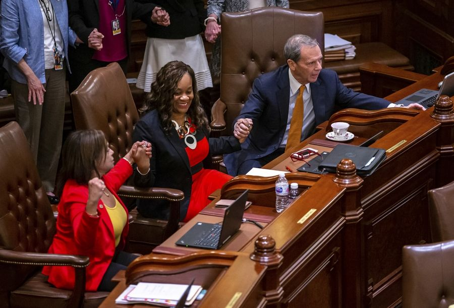 Senate President John Cullerton, D-Chicago, joins hands with Sens. Kimberly A. Lightford, center, D-Maywood, and Iris Martinez, left, D-Chicago, as they vote on the Reproductive Health Act on the floor of the Senate at the State Capitol, Friday, May 31, 2019, in Springfield, Ill. (Justin L. Fowler/The State Journal-Register via AP)