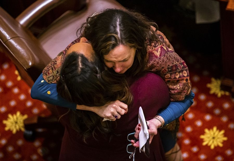 Rep. Kelly Cassidy, D-Chicago, is hugged by Sen. Toi Hutchinson, D-Olympia Fields, as they celebrate Senate passage of the Reproductive Health Act, at the State Capitol, Friday, May 31, 2019, in Springfield, Ill. (Justin L. Fowler/The State Journal-Register via AP)