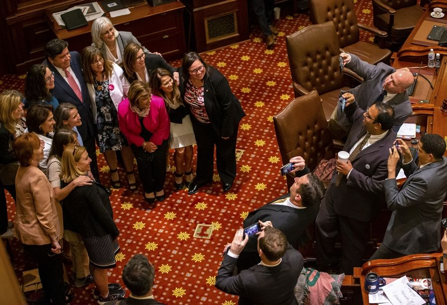 Illinois Gov. J.B. Pritzker is joined by Sen. Melinda Bush, D-Grayslake, with pink button, and Rep. Kelly Cassidy, D-Chicago, with glasses and blue clothing, and women from the floor of the Illinois Senate to celebrate Senate passage of the Reproductive Health Act on Friday, May 31, 2019, at the Capitol in Springfield, Ill. (Justin L. Fowler/The State Journal-Register via AP)