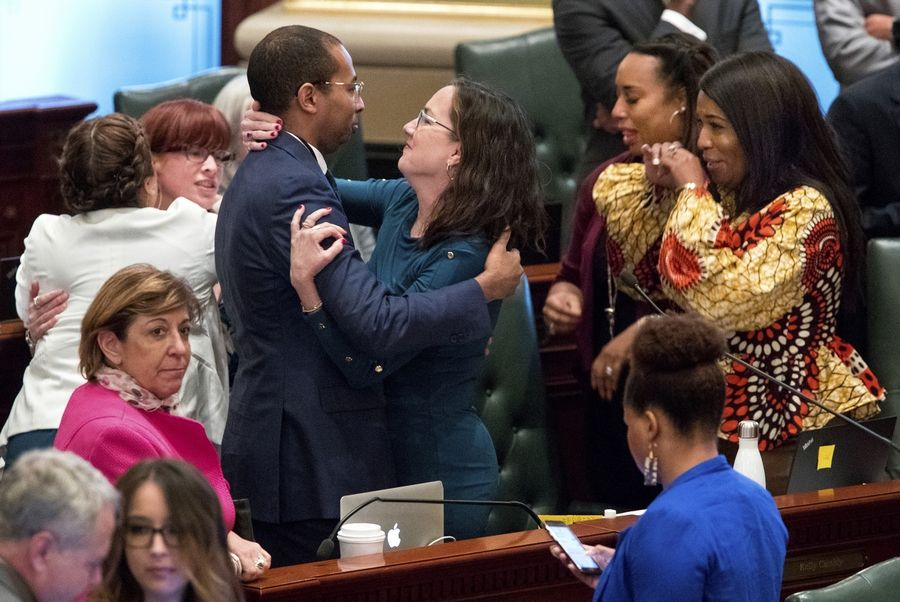 Illinois deputy governor Christian Mitchell and Illinois state Rep. Kelly Cassidy, D-Chicago, embrace as they celebrate the 66-47 vote in the Illinois House for a bill to legalize recreational marijuana use Friday, May 31, 2019. The vote sends the bill to Gov. J.B. Pritzker who indicated he will sign it. (Ted Schurter/The State Journal-Register via AP)