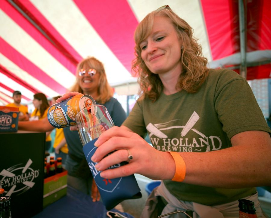 Tracy Bratzke of New Holland Brewing pours a sample of their Tangerine Spice Machine during the Grayslake Craft Beer Festival in downtown Grayslake Saturday.
