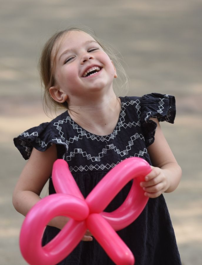 June Barr, a 5-year-old from Oswego, whose grandparents are from Wheaton, dances and plays with her balloon during the Taste of Wheaton on Saturday.