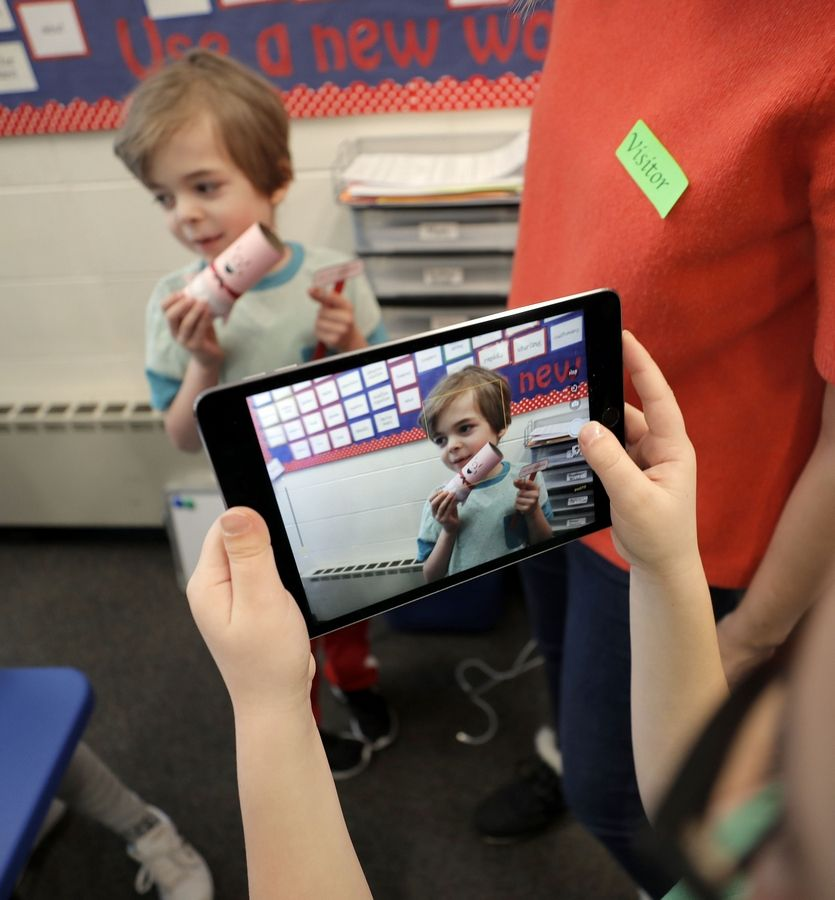 A student in Julie Serrecchia's fourth-grade class takes video of Noah Wood, 7, during one of his monthly visits to their classroom as part of the Nora Project, which aims to foster friendship and empathy between students and their peers with disabilities.