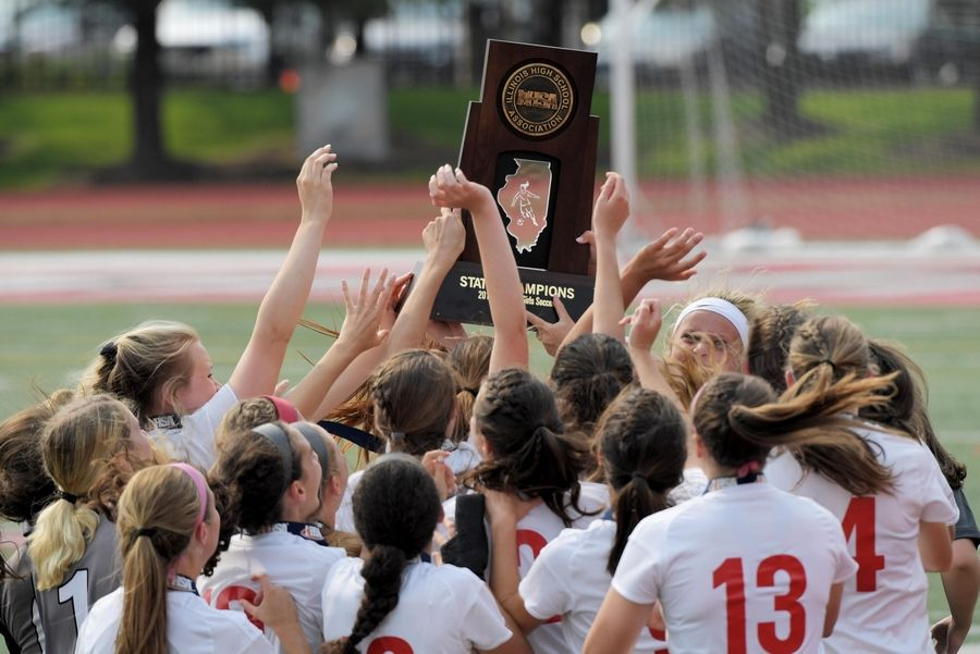 Benet Academy lifts the state championship trophy after defeating Wauconda in the Class 2A state girls soccer final at North Central College in Naperville Saturday.