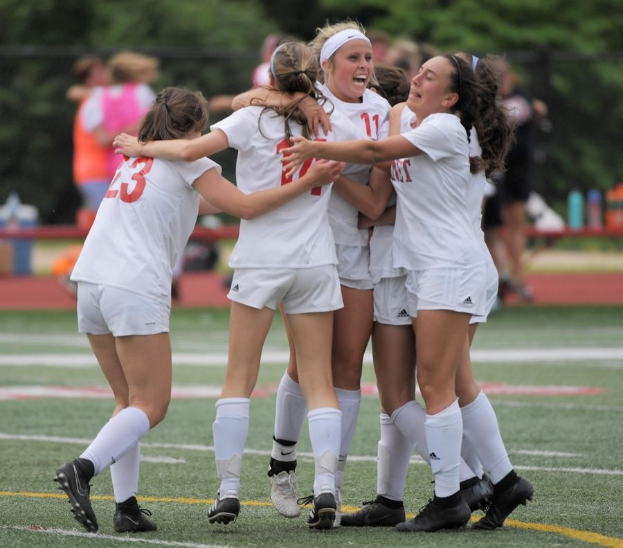 Benet Academy's Mary Kate Hansen is surrounded by teammates after her game-tying goal with less than two minutes in regulation play against Wauconda in the Class 2A state girls soccer final at North Central College in Naperville Saturday.