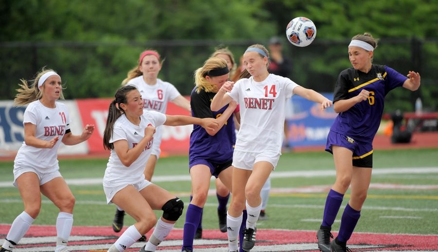 Wauconda's Abigail McHugh, middle, gets the header for a goal in a pack of Benet Academy players in the Class 2A state girls soccer final at North Central College in Naperville Saturday.