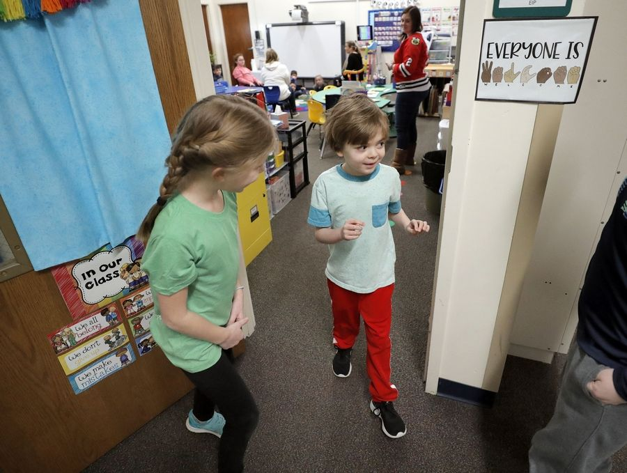 Fourth-grader Faith Flayter leads Noah Wood, 7, out of his special education class en route to a visit with students in her classroom at Butterfield School in Libertyville.