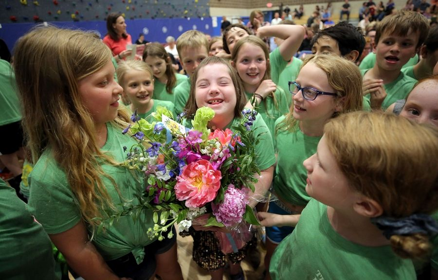 WATCH AT DAILYHERALD.COM/VIDEO: Avery Strons holds flowers and grins as she is surrounded by other Rockland School third-graders during the Nora Night Film Festival at Copeland School in Libertyville.