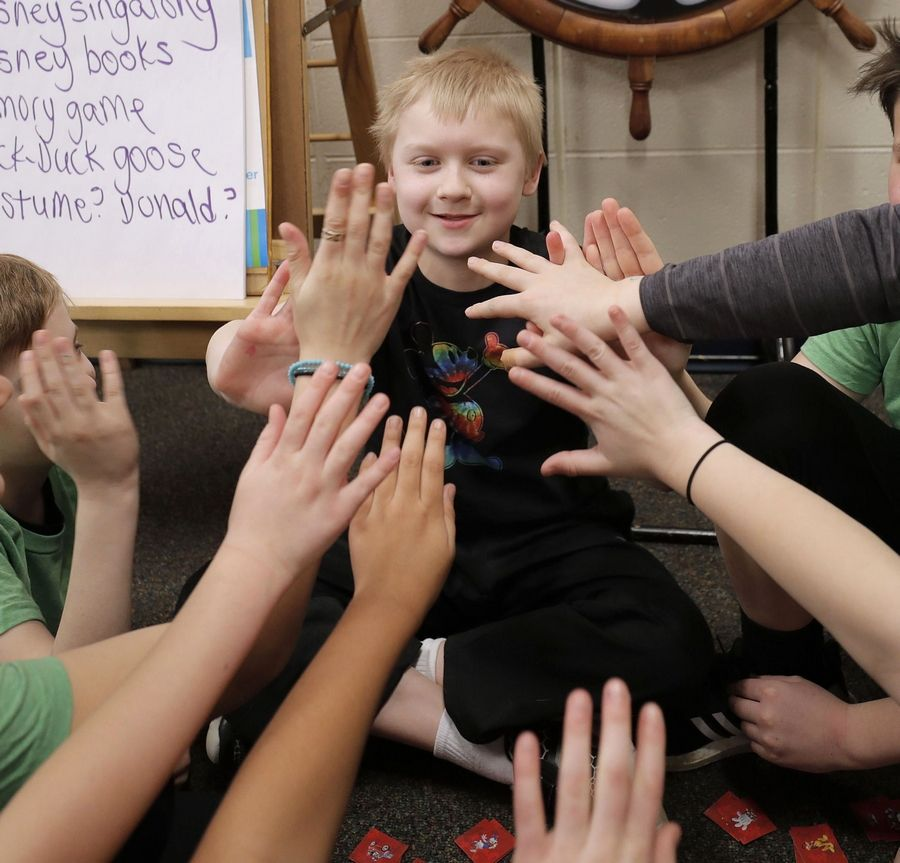 Nolan Finch, 9, gets high-fives from friends in teacher Julie Serrecchia's fourth-grade class as he visits with students at Butterfield School in Libertyville.