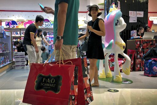 "In this Saturday, June 1, 2019, photo, a man carries a paper bags containing toys purchased from the FAO Schwarz as people shop at the newly open FAO Schwarz toy store at the capital city's popular shopping mall in Beijing. China has issued a report blaming the United States for a trade dispute and says it won't back down on ""major issues of principle."" The statement from the Cabinet spokesman's office on Sunday says China has kept its word throughout 11 rounds of talks and will honor its commitments if a trade agreement is reached."