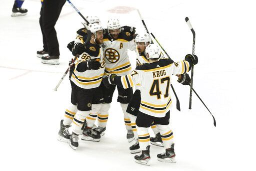 Boston Bruins center Patrice Bergeron (37) celebrates with teammates after scoring against the St. Louis Blues during the first period of Game 3 of the NHL hockey Stanley Cup Final Saturday, June 1, 2019, in St. Louis.