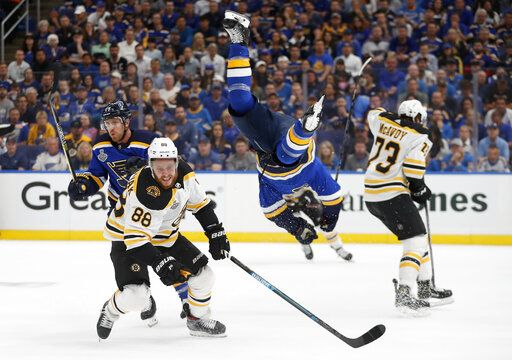 St. Louis Blues center Brayden Schenn, second from right, flips past Boston Bruins right wing David Pastrnak (88), of the Czech Republic, during the first period of Game 3 of the NHL hockey Stanley Cup Final Saturday, June 1, 2019, in St. Louis.