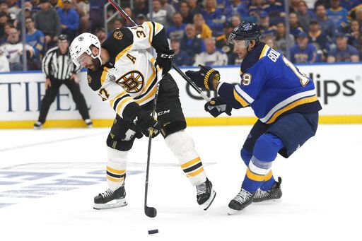 Boston Bruins center Patrice Bergeron (37) passes the puck away from St. Louis Blues defenseman Jay Bouwmeester (19) during the first period of Game 3 of the NHL hockey Stanley Cup Final Saturday, June 1, 2019, in St. Louis.