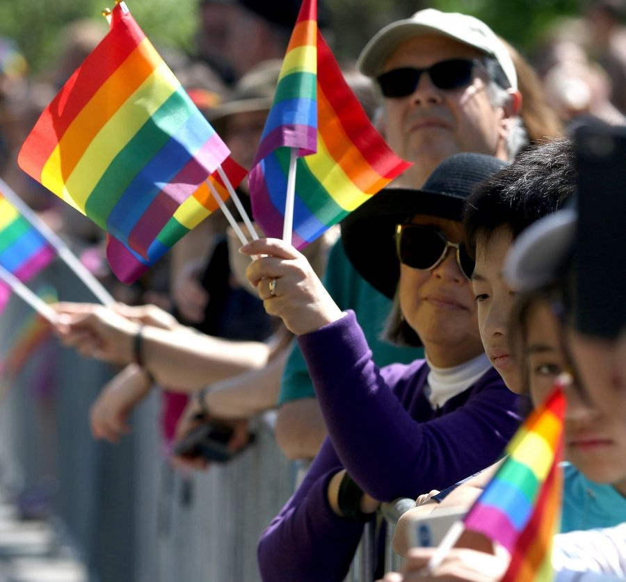 Kyung Wohlner of Arlington Heights waves flags Sunday during the first Buffalo Grove Pride Parade.