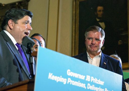 Illinois Senate Republican Leader Bill Brady, R-Bloomington, stands with Illinois Governor J.B. Pritzker as he holds a press conference, surrounded by both Republicans and Democrats from the legislature, touting the accomplishments of the Spring Session after the Illinois Senate approved funding for the capital construction plan, legalized sports betting and gambling expansion, Sunday, June 2, 2019, in Springfield, Ill. (Justin L. Fowler/The State Journal-Register via AP)