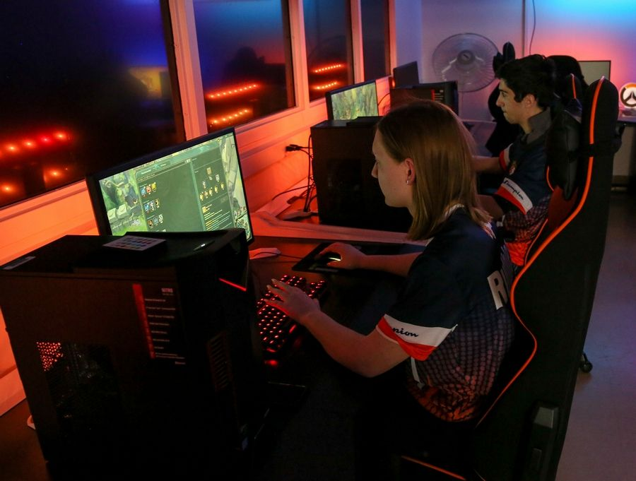 "Naperville North High School junior Stacy Buchner, left, and senior Onur Yorulmazoglu play League of Legends in an ""arena"" specifically designed for esports. A similar lab is being created at Naperville Central."