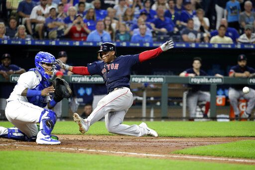 Boston Red Sox's Rafael Devers beats the tag at home by Kansas City Royals catcher Martin Maldonado to score on a double by Brock Holt during the sixth inning of a baseball game Tuesday, June 4, 2019, in Kansas City, Mo.