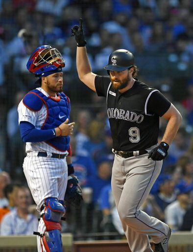 Colorado Rockies' Daniel Murphy right, celebrates at home plate after hitting a solo home run while Chicago Cubs catcher Victor Caratini left, looks on during the fourth inning of a baseball game Tuesday, June 4, 2019, in Chicago.
