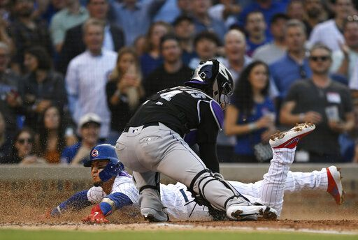 Chicago Cubs' Javier Baez slides into home plate safely on a Carlos Gonzalez double as Colorado Rockies catcher Tony Wolters attempts to apply the tag during the second inning of a baseball game Tuesday, June 4, 2019, in Chicago.
