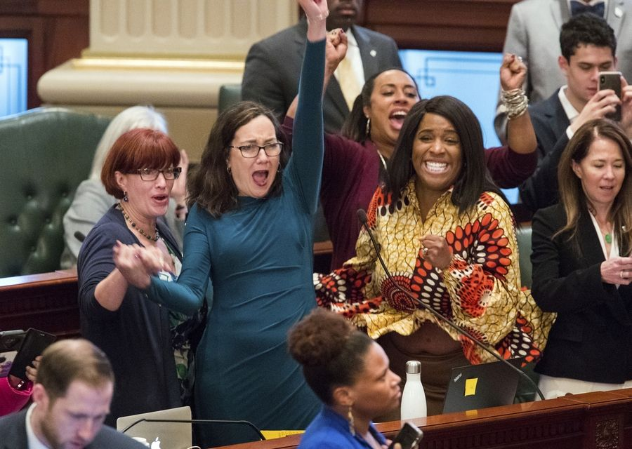 Illinois state Rep. Kelly Cassidy, a Chicago Democrat, celebrates Friday with Illinois state Senator Heather Steans, a Chicago Democrat, left, and Rep. Jehan Gordon-Booth, a Peoria Democrat, as they watch the final votes come in for their bill to legalize recreational marijuana use in the Illinois House chambers Friday. The 66-47 vote sends the bill to Gov. J.B. Pritzker who indicated he will sign it.