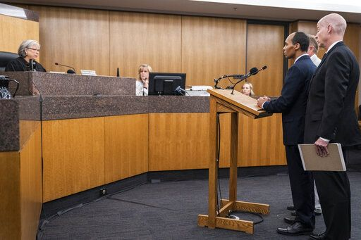 Former Minneapolis police officer Mohamed Noor, standing with his lawyers Thomas Plunkett, closest to camera, and Peter Wold, behind Noor, is sentenced by Judge Kathryn Quaintance at the Hennepin County District Court Friday, June 7, 2019, in Minneapolis, in the fatal shooting of Justine Ruszczyk Damond. (Leila Navidi/Star Tribune via AP, Pool)