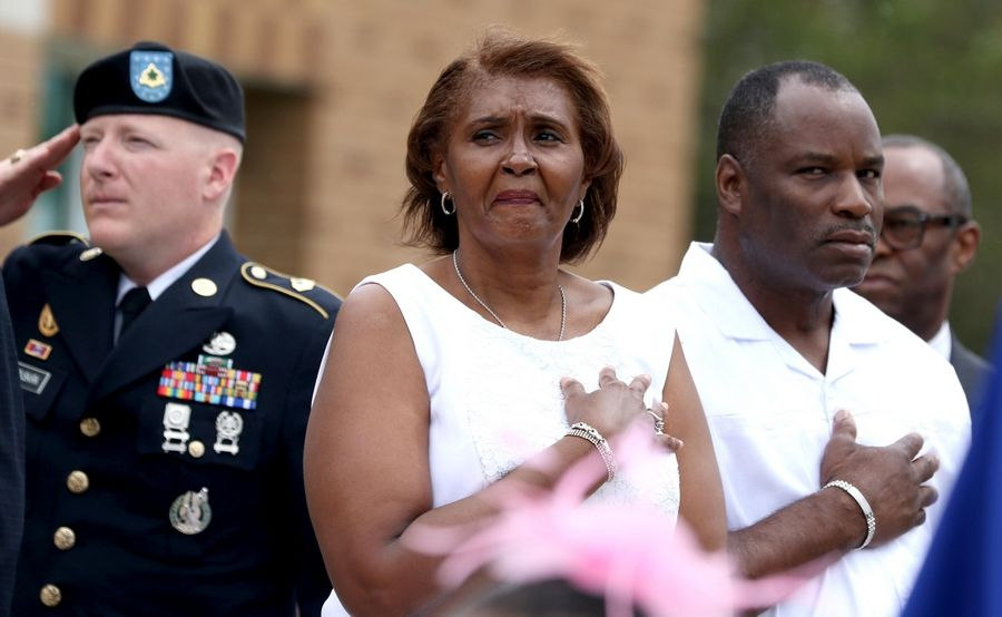 Sandra Williams Smith, center, her husband Aron Smith, right, and Sgt. 1st Class Derek Vanbuskirk, left, listen Saturday to the national anthem at the newly renamed Cpl. Jeffrey Allen Williams Post Office in Warrenville. Her 20-year-old son was mortally wounded by an improvised explosive device in northwestern Iraq in September 2005.
