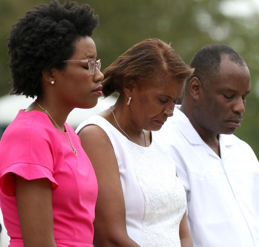 U.S. Rep. Lauren Underwood observes a moment of silence with Jeffrey Allen Williams' mother, Sandra Williams Smith, and his stepfather, Aron Smith, Saturday at the Warrenville post office.