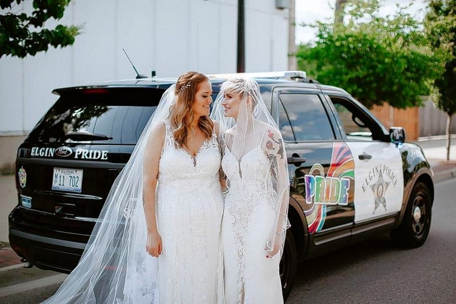 Newlyweds Seda, left, and Lindsey Lachanski said that getting to take photos with the Elgin Police Department's new LGBTQ squad car added to the joy of their June 2 wedding in Elgin.