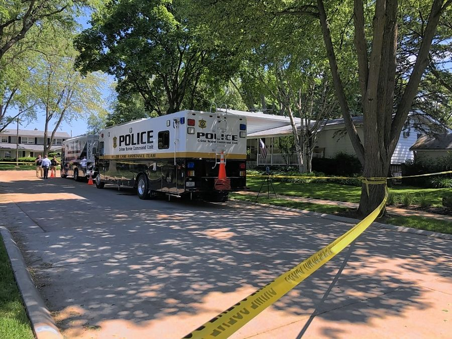 Arlington Heights police are holding a person of interest in the homicide of a man and woman found early Saturday inside their home on South Derbyshire Lane.