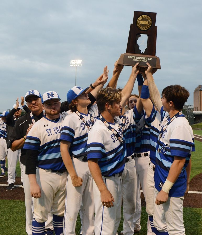 St. Charles North players hold up their state runner-up trophy following a 3-2 loss in eight innings to Edwardsville during the Class 4A state championship game in Joliet Saturday.