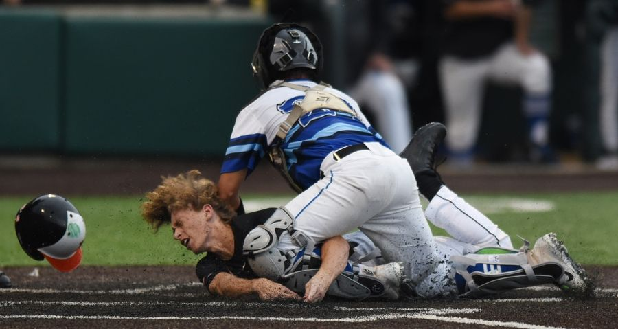 Edwardsville's Aaron Young scores the go-ahead run in the eighth inning under the tag by St. Charles North's Marco Torres.