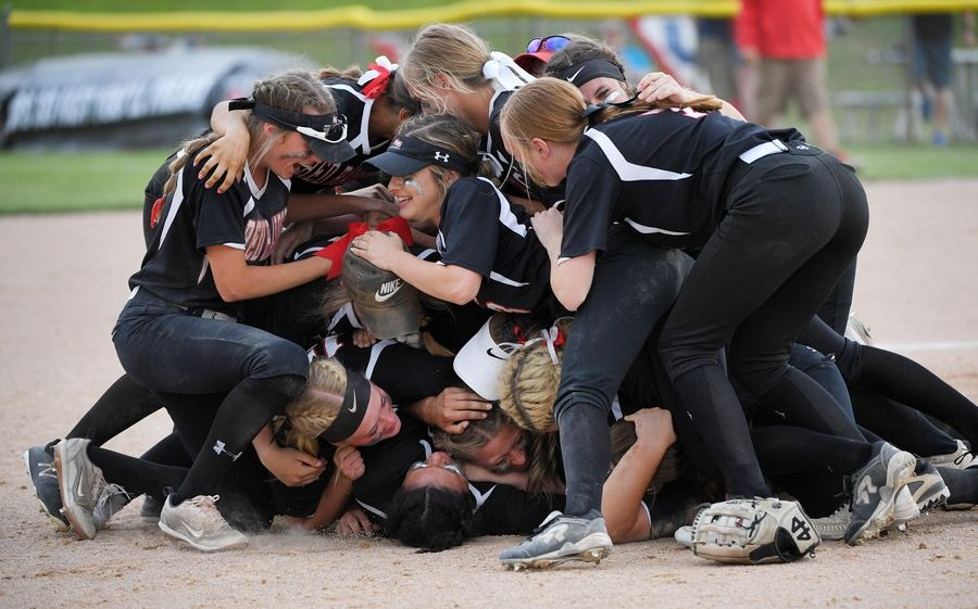 The Huntley Red Raiders pile on pitcher Brianna Bower after winning the Class 4A state softball final game against St. Charles East in Peoria Saturday.
