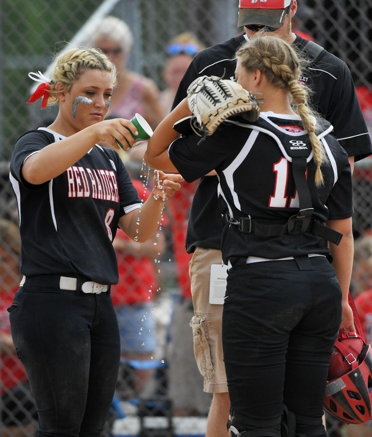 Huntley's Sofia Tenuta pours water on the scraped elbow of catcher Lindsay Morgan after she dove for a foul ball against St. Charles East in the Class 4A state softball final game in Peoria Saturday.