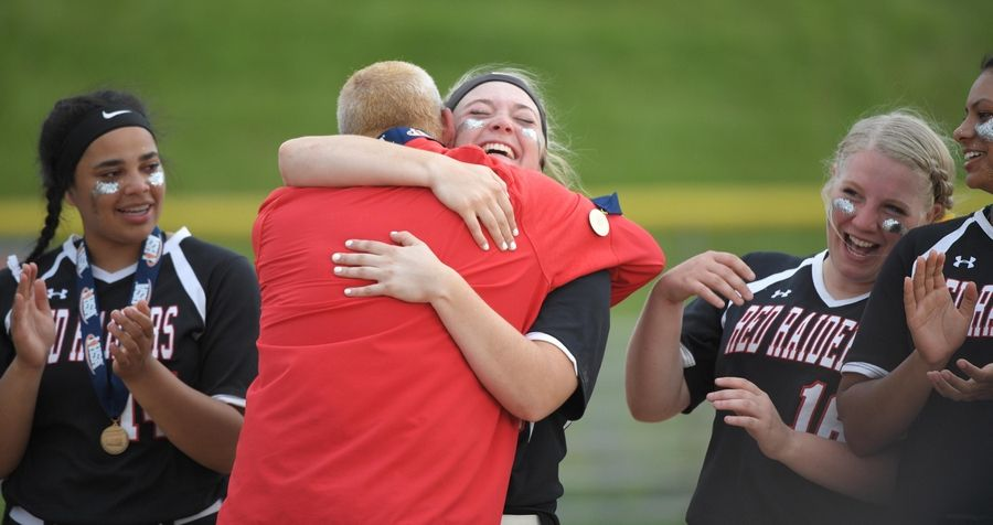 Huntley head coach Mark Petryniec hugs Grace Kutz after handing out medals in the Class 4A state softball final game in Peoria Saturday.