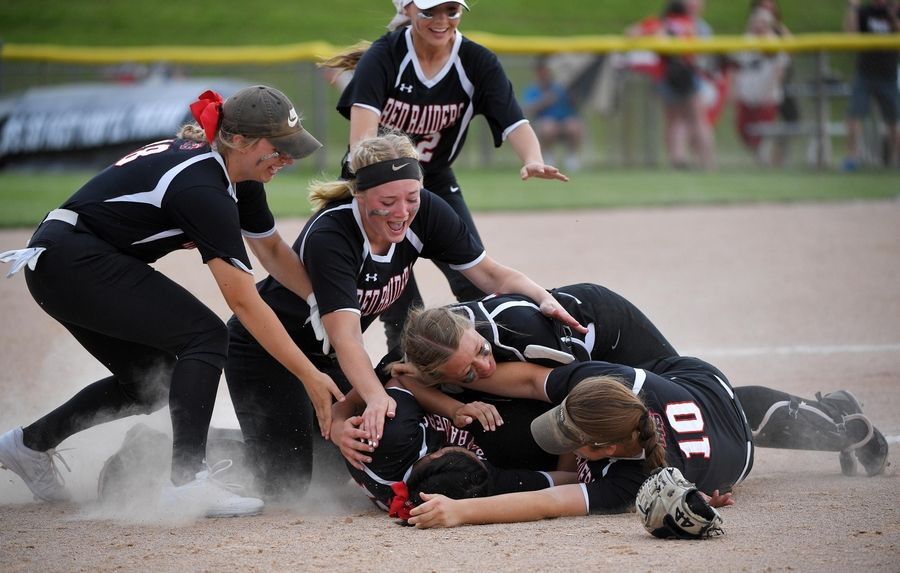 Huntley'sBriana Bower is swarmed by teammates after she struck out the final batter in the eighth inning to win the Class 4A state softball final game in Peoria Saturday.