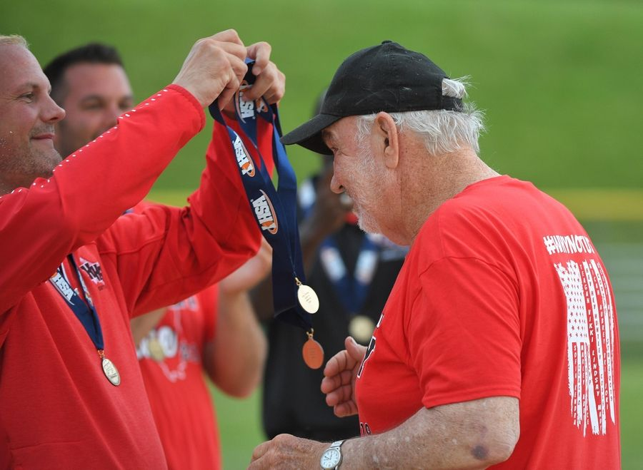 Huntley head coach Mark Petryniec gives an honorary medal to James Overstreet, a longtime Huntley sports supporter, after the Class 4A state softball final game in Peoria Saturday.