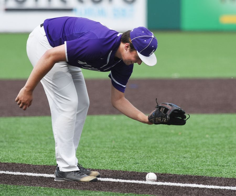 Hampshire pitcher Matthew Jachec picks up a bunted ball which has come to a rest inside the line during the Class 4A state baseball third-place game against St. Rita in Joliet Saturday.