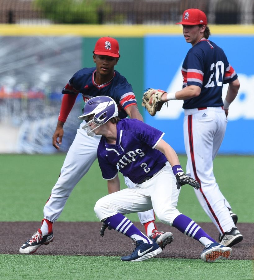 Hampshire's Gavin Kriegel gets tagged out by St. Rita shortstop Jalen Greer after being caught in a rundown between first and second during the Class 4A state baseball third-place game in Joliet Saturday.