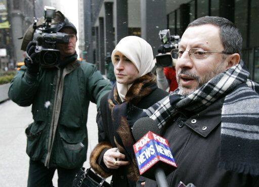 FILE - In this Feb. 1, 2007 file photo, Abdelhaleem Ashqar is surrounded by cameramen as he leaves federal court with his wife, in Chicago. Ashquar who says he fears torture at the hands of Israeli authorities,  is back in the U.S. after a judge's order forced immigration authorities to reverse his deportation and bring him back from Israel before he ever got off the plane.  According to court papers and interviews, U.S. authorities arrested and deported Ashqar Tuesday, June 4, 2019  after misleading him about his need to report to an immigration office to process paperwork.