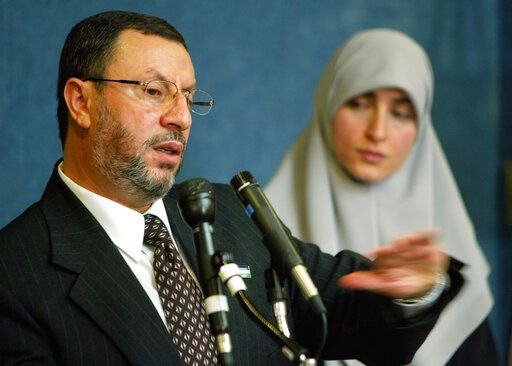 FILE - In this Feb. 16, 2004 file photo,  Abdelhaleem Ashqar, left, with his wife Asma, right, meets reporters at the National Press Club in Washington, to announce his presidential candidacy for the Palestinian National Authority.  Ashquar who says he fears torture at the hands of Israeli authorities,  is back in the U.S. after a judge's order forced immigration authorities to reverse his deportation and bring him back from Israel before he ever got off the plane.  According to court papers and interviews, U.S. authorities arrested and deported Ashqar Tuesday, June 4, 2019  after misleading him about his need to report to an immigration office to process paperwork.