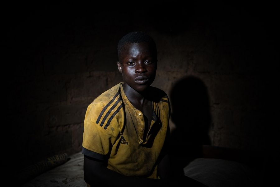 Karim Bakary, 16, from Burkina Faso, photographed inside a hut out in the woods near the cocoa farm where he works and sometimes take shelter in with other children.