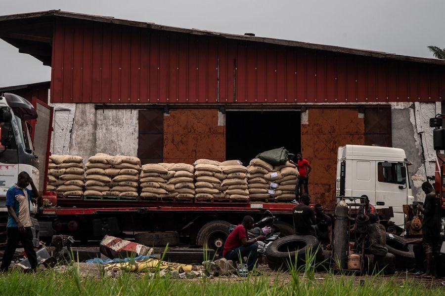 Men unload bags of cocoa near the office of Cargill, one of the leading cocoa suppliers for the chocolate industry.
