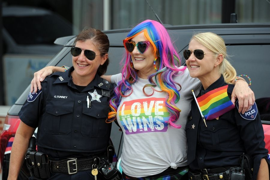 Aurora police officer Chris Tunney and Chief Kristen Ziman take a picture Sunday with Tara Vago of Aurora before the start of the second annual Aurora Pride Parade.