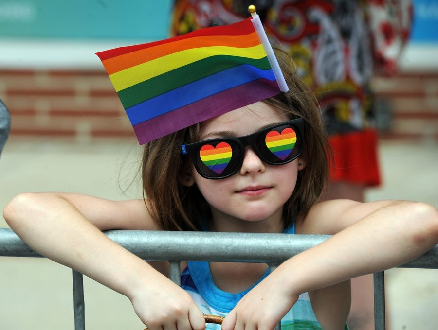 Nadia Cirone, 8, of Oswego cheers on marchers Sunday in the second annual Aurora Pride Parade.